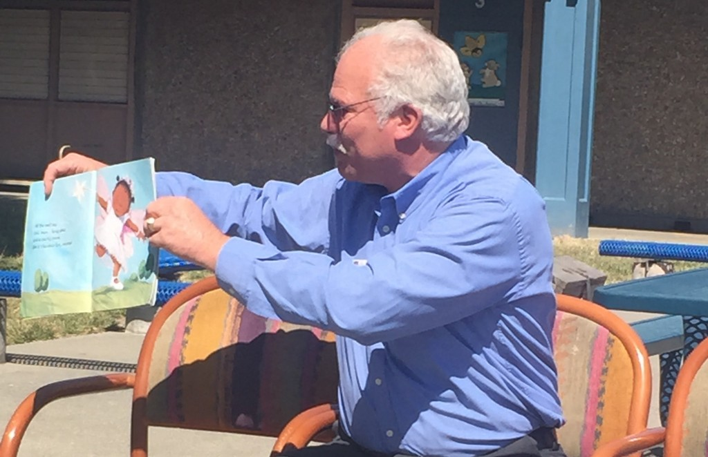 Man reading a book to kids